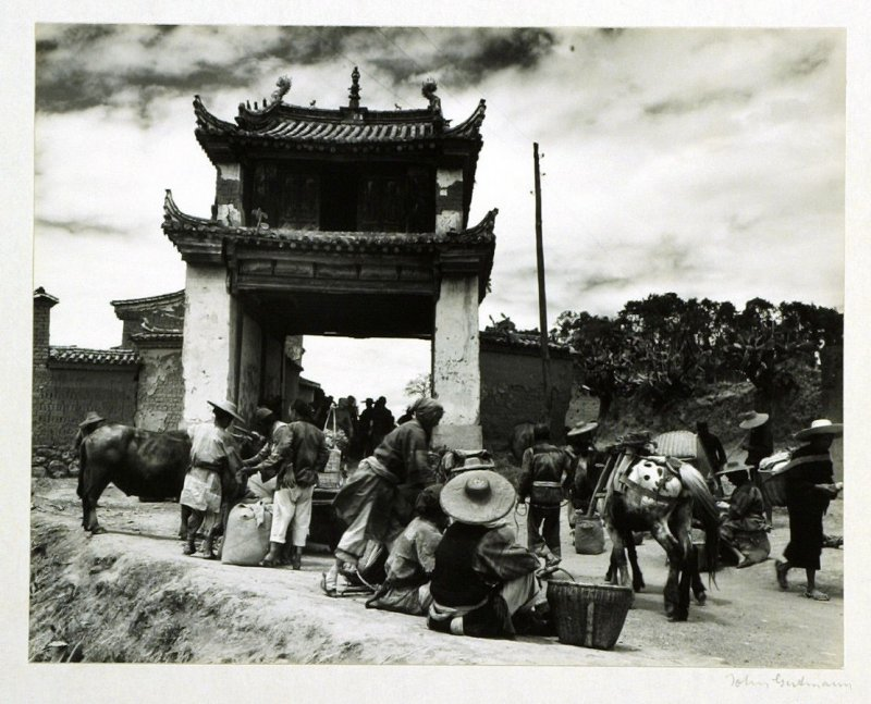 Trading begins at the road through the gateway leading to the big county market of Chengkung, Yunnan Province.