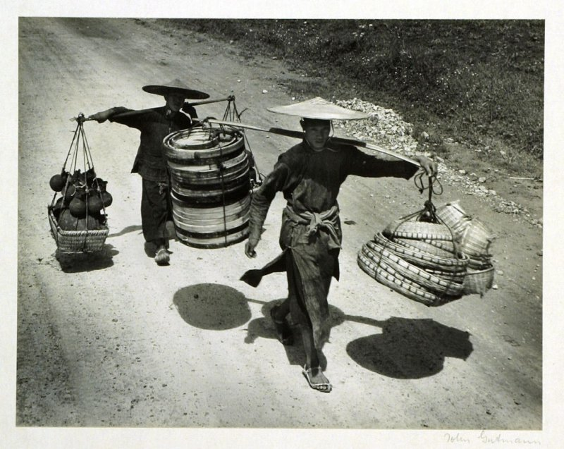Kweichow craftsmen going to the market with their loads of pottery, bamboo woven baskets and riddles for winnowing rice.