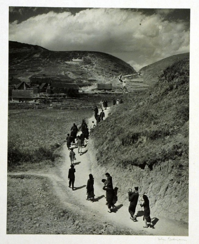 The pilgrim's long stretched line on the path between the hills to the Temple of the Blue Mountain. On the hill in the distance a wealthy family's private mausoleum.