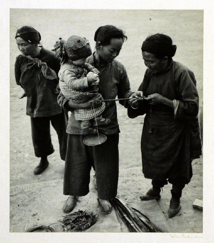 Yunnanese women reading a scale. Throughout China younger women have abandoned the custom of bound feet which is still perceptible on the older woman.