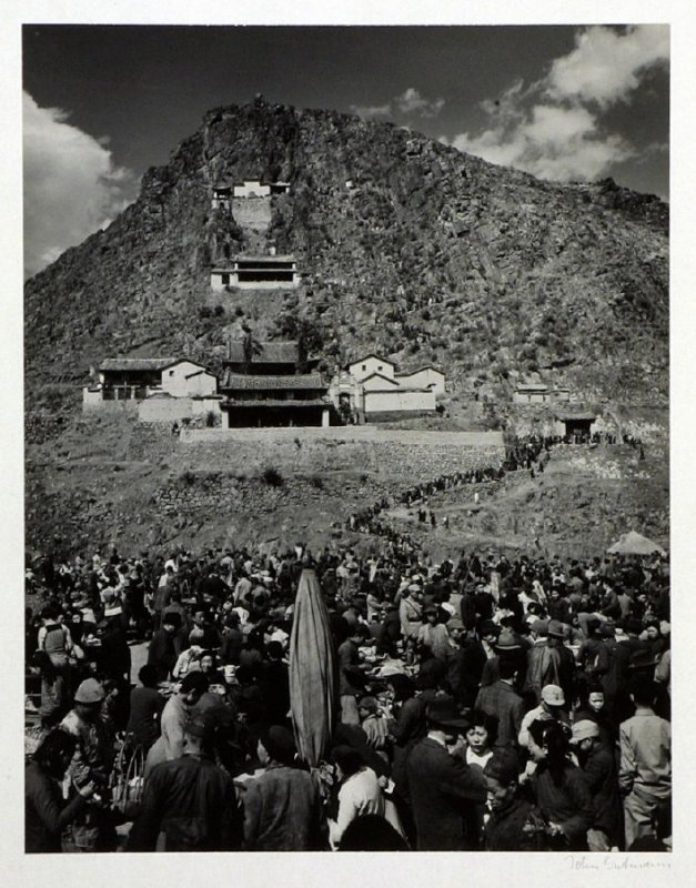 "The three main buildings of a Buddhist temple nesting in the rocks of the ""Blue Mountain"" The zig-zag path is filled with climbing pilgrims, as seen from one fo the picnic places where everybody rests and feeds before going up the last stretch. The pilgri"