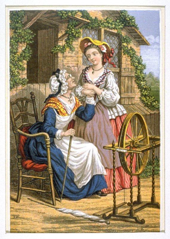 Two women next to a spinning wheel