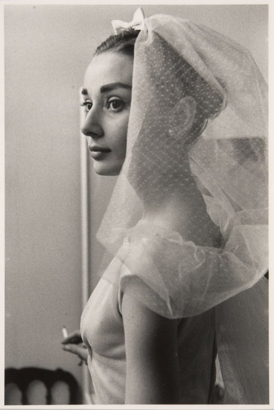 """Audrey Hepburn in a wedding dress with cigarette on the set of """"Funny Face,"""" Paris, 1956"""