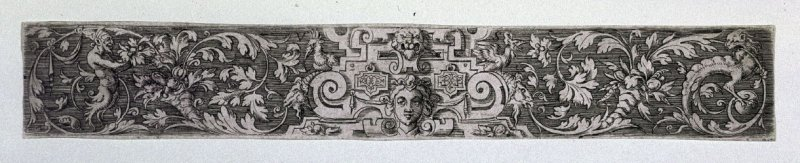 Frieze with architectural ornament showing heads of a woman and a lion; at each side, foliage with grotesques. White on dark background. Initials V-S