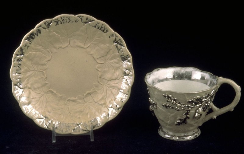 Cup and saucer with leaf and acorn designs